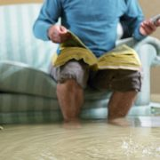Picture of a man sitting on a couch in a room filled with water