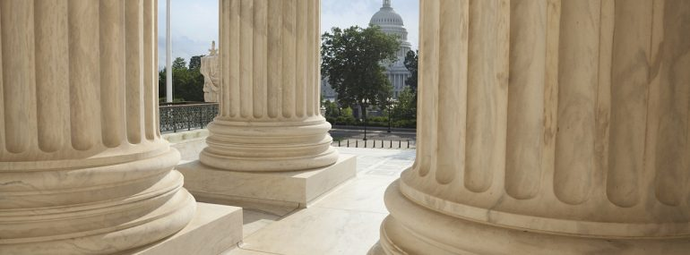 Photo of US Supreme Court columns with US Capitol in the background