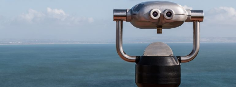 Sightseeing binoculars overlooking the ocean from a high vantage point