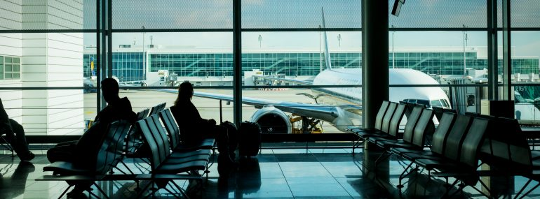 Image shows passengers in an airport terminal waiting area.