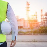 Image shows a man with a safety hat standing near an oil refinery.