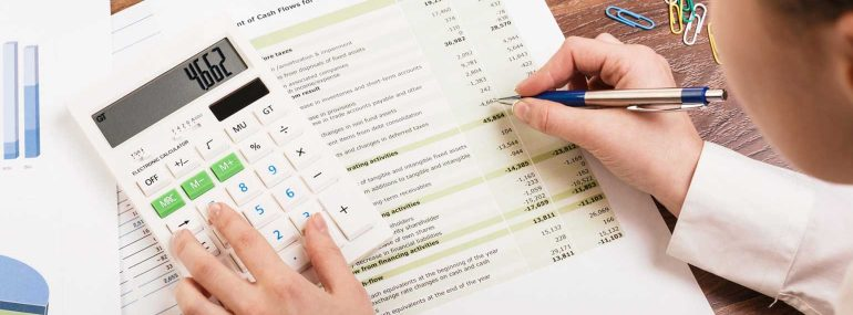 Woman with calculator and financial analysis form