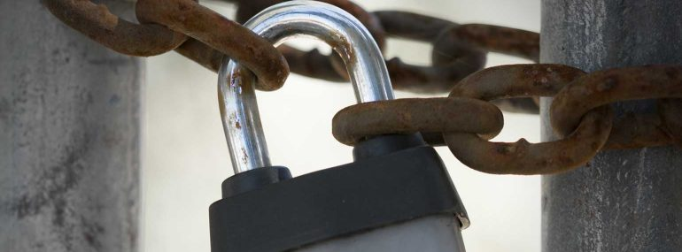 Padlock around rusted chain link