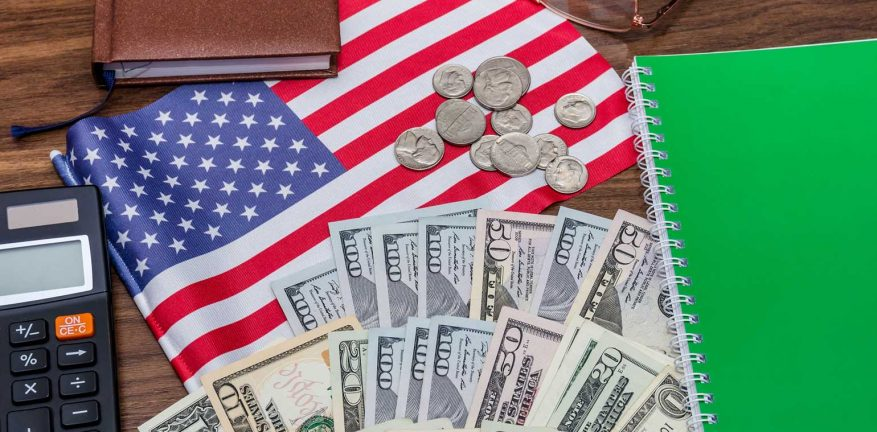 US flag on desk with money