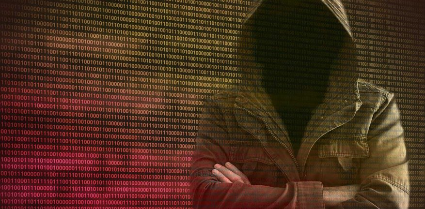 Hooded hacker against a wall of binary code