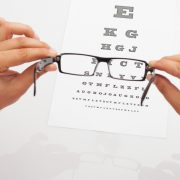 Looking through eyeglasses at an eye chart