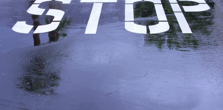 Stop-sign-written-on-wet-pavement
