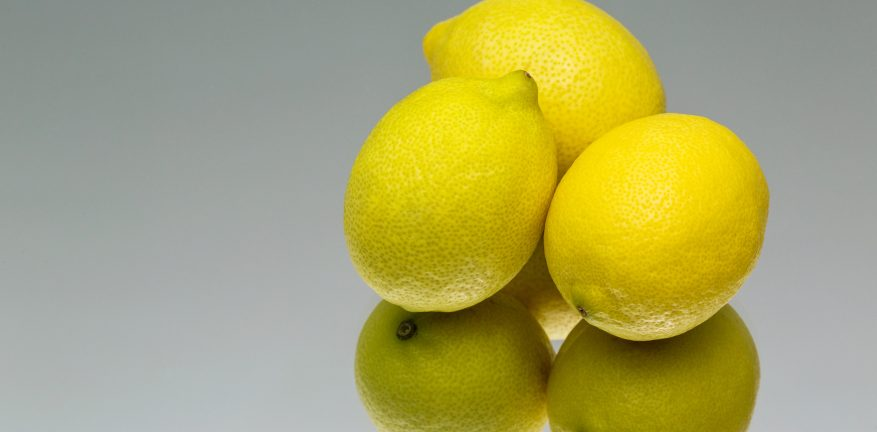 Three lemons on a reflective surface.