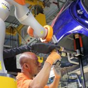 Robots and people work side by side in a Ford plant.