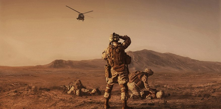 Photo of military personnel on a barren landscape with a helicopter in the air