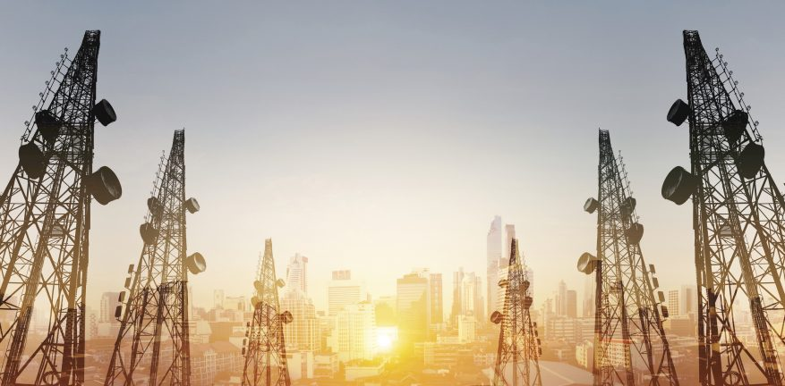 Image of telecommunications towers with antennas and cityscape