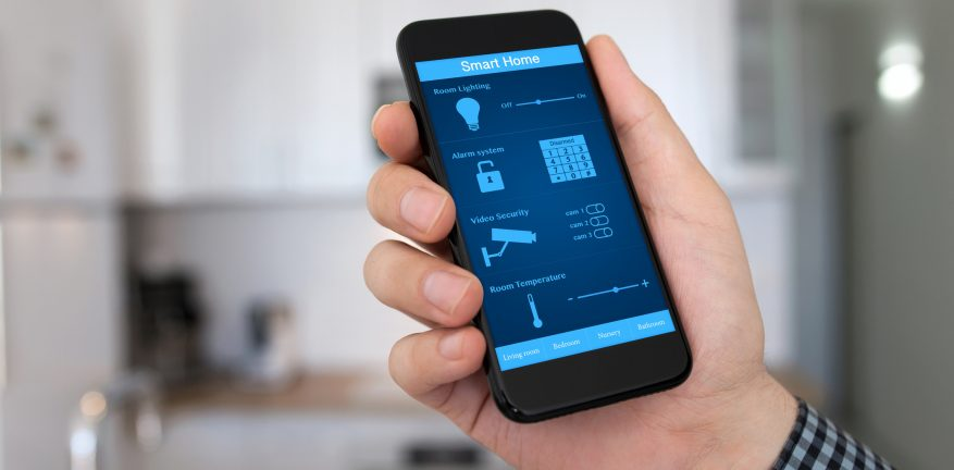 Image of man holding smartphone in a house