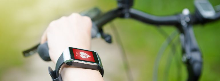 Image of woman riding bike with a smart watch heart rate monitor