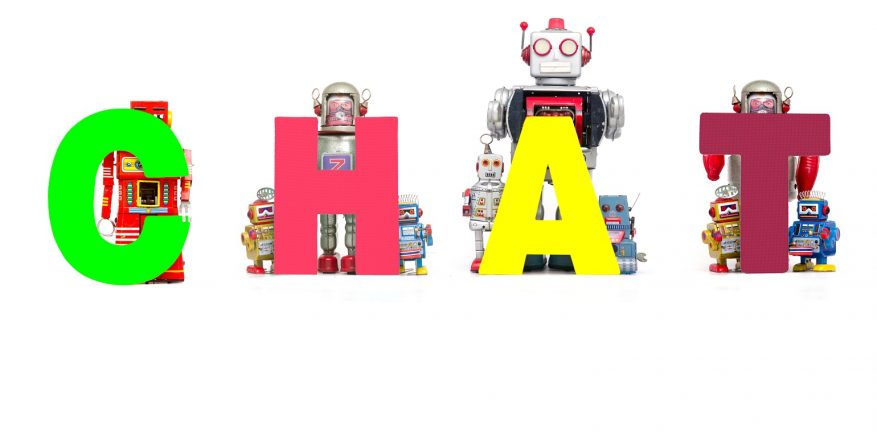 vintage toy robots holding up the word CHAT
