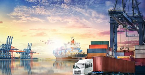 Logistics import/export background and transport industry of container truck and cargo ship with working crane bridge in shipyard at sunset sky