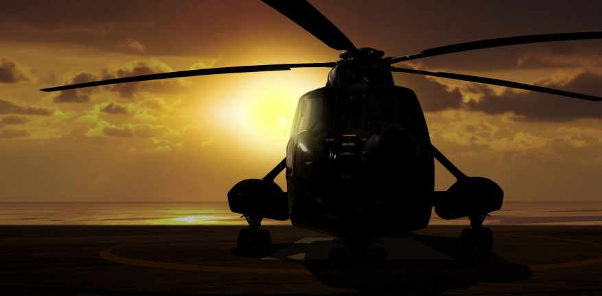 Image shows a military helicopter on carrier ship at sunset.