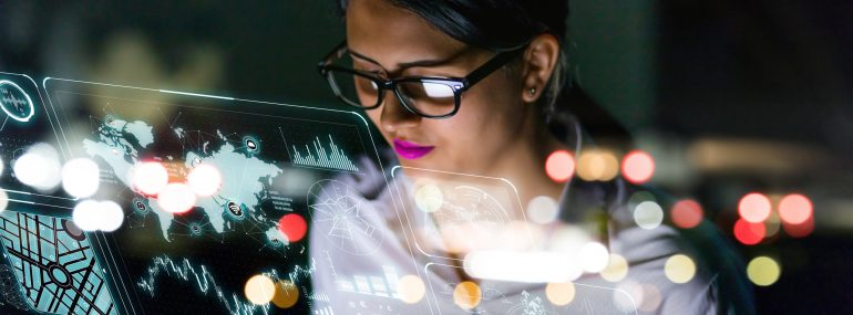 Image shows female engineer looking at information on the screen of futuristic interface.