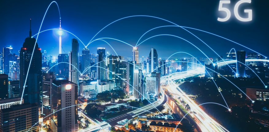 Image shows 5G network wireless systems and internet of things with modern city skyline.