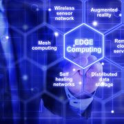 IT expert in a blue suit touches a hexagon tile  with the words edge computing surrounded by specific keywords