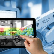 Image shows an Industry 4.0 concept with a man holding a tablet with augmented reality screen software and a wireless robot arm in a smart factory background
