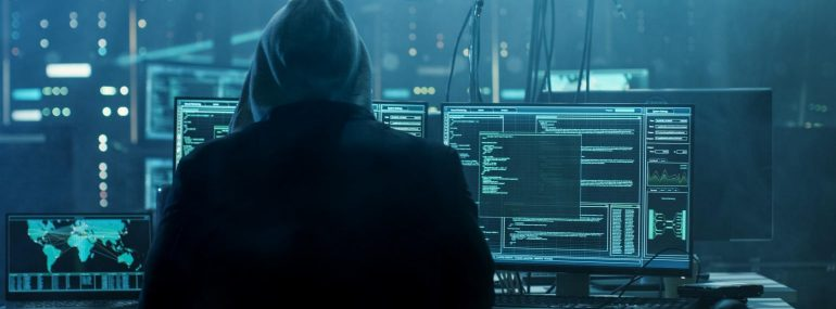 Image shows a hooded hacker breaking into data servers.