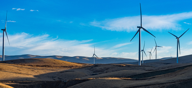 Image shows giant wind turbines overlooking a hillside..