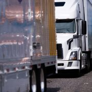 Convoy of big rigs customized semi trucks in different colors and different styles and models with semi trailers driving side by side as if competing which one of them stronger on a spacious multi-lane highway