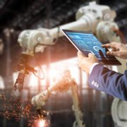 Image shows an industrial engineer using tablet check and control automation robot arms machine in intelligent factory industrial on real time monitoring system software. Welding robotics and digital manufacturing operation. Industry 4.0 concept