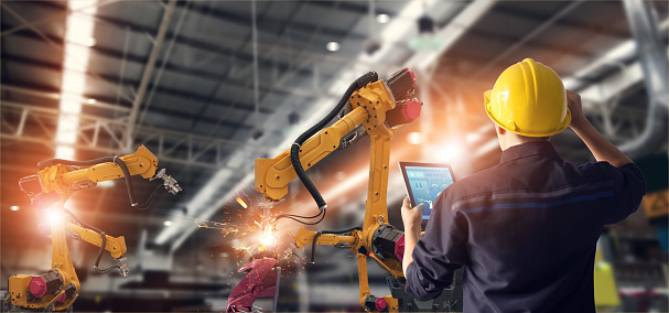 Image shows an engineer using tablet check and control automation robot arms machine in intelligent factory industrial on monitoring system software. Welding robotics and digital manufacturing operation.