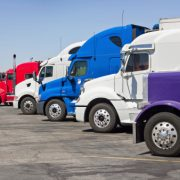 Image shows multiple trucks parked in a large parking lot.