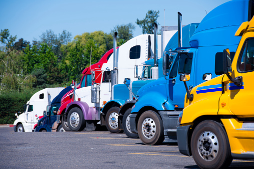 Image shows a fleet of semi trucks parked together.