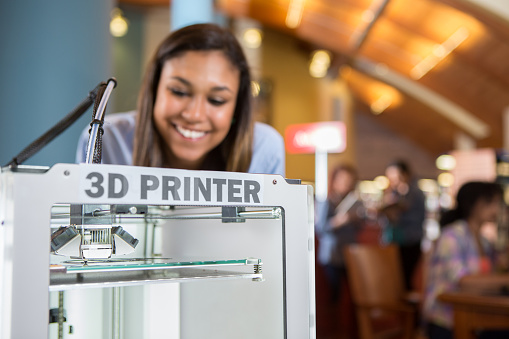 Image shows a 3D printer being used by college student in library makerspace