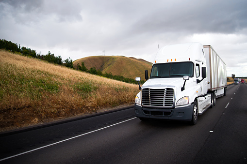 Image shows a big rig semi truck driving along a highway.