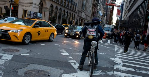 A bike messenger delivering a package in the city.