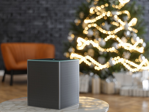 Image shows a smart speaker near a Christmas tree.