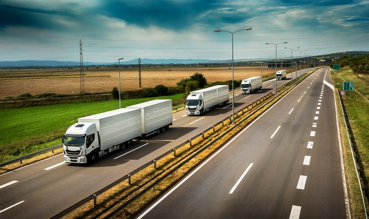 Image shows a caravan or convoy of trucks in line on a country highway.