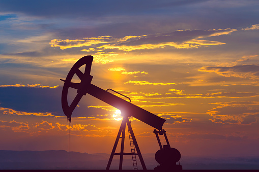 Image show an oil pump on the background of the sunset.
