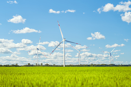 Image shows a wind power plant in the green field against cloudy sky.