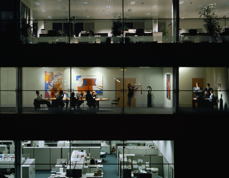 Image shows a meeting happening inside an office building.