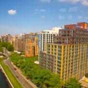 Image shows an aerial view of East River and new residential buildings on Roosevelt Island, looking north, from Roosevelt Island Tram, New York City.