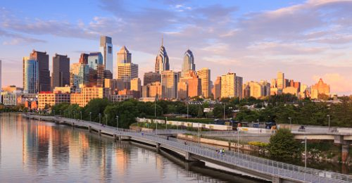 Image shows the Philadelphia skyline with the Schuylkill River.