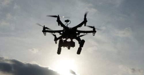 Image shows a drone taking aerial photos at sunset.