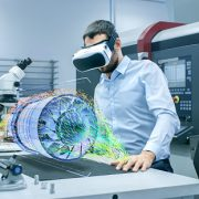 Image shows a factory engineer wearing VR headset designing an engine turbine on a holographic projection table.