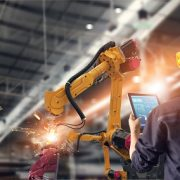 Image shows welding robotics and a digital manufacturing operation.